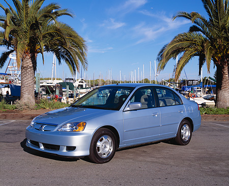 AUT 38 RK0063 02 © Kimball Stock 2003 Honda Civic Hybrid Silver Blue Metallic 3/4 Front View On Pavement By Palm Trees At Harbor