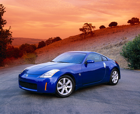 AUT 38 RK0071 07 © Kimball Stock 2003 Nissan 350Z Blue 3/4 Front View On Pavement Dry Grass Hill Filtered