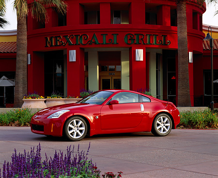 AUT 38 RK0075 02 © Kimball Stock 2003 Nissan 350Z Red 3/4 Side View On Pavement By Restaurant