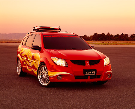 AUT 38 RK0111 04 © Kimball Stock 2003 Pontiac Vibe GT Red Yellow Graphics Surfboard Suspension Techniques 3/4 Front On Pavement Filtered