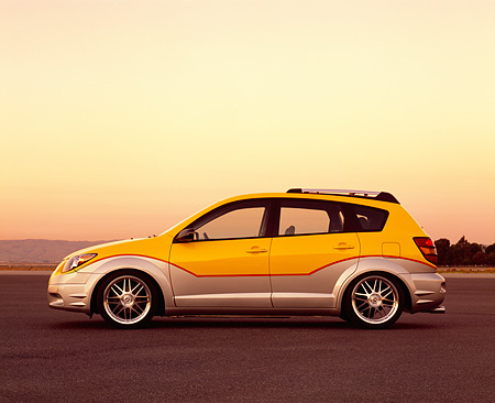 AUT 38 RK0119 01 © Kimball Stock 2003 Pontiac Vibe Yellow And Silver Super Charged Suspension Techniques Profile On Pavement Filtered