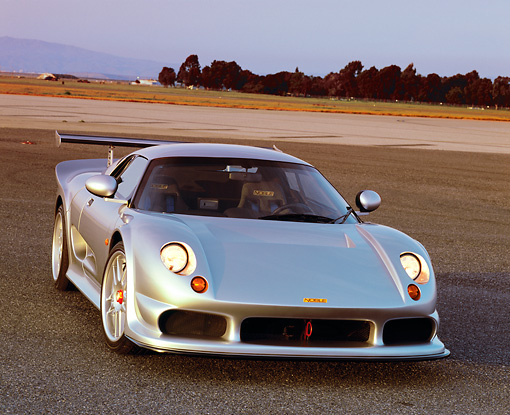 AUT 38 RK0236 01 © Kimball Stock 2003 GSR Noble M12 GTO Silver 3/4 Front View On Pavement Trees Background Filtered