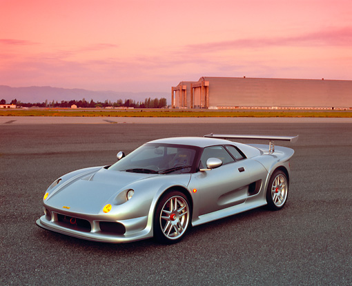 AUT 38 RK0237 02 © Kimball Stock 2003 GSR Noble M12 GTO Silver 3/4 Front View On Pavement Airplane Hanger Background Filtered
