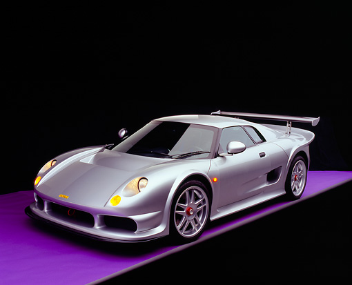 AUT 38 RK0242 03 © Kimball Stock 2003 GSR Noble M12 GTO Silver 3/4 Front View On Purple Floor Studio