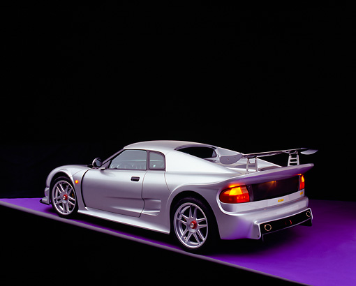 AUT 38 RK0244 10 © Kimball Stock 2003 GSR Noble M12 GTO Silver 3/4 Rear View On Purple Floor Studio