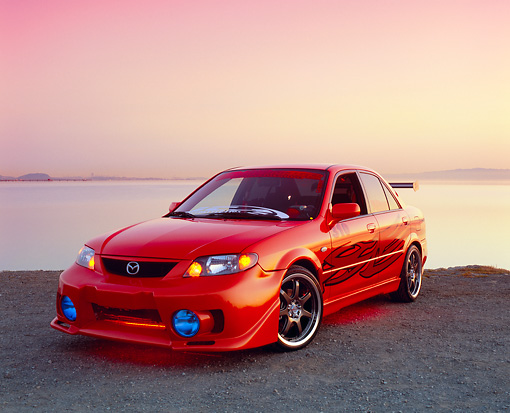 AUT 38 RK1865 02 © Kimball Stock 2003 Mazda Protege Orange Red Flames Custom 3/4 Front View On Gravel By Water Filtered