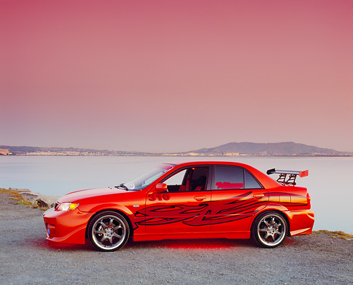 AUT 38 RK1870 03 © Kimball Stock 2003 Mazda Protege Orange Red Flames Profile View On Dirt By Water