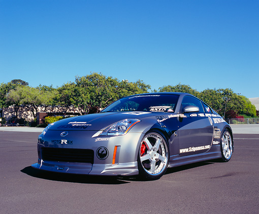 AUT 38 RK1872 03 © Kimball Stock 2003 Nissan 350Z Custom Silver Low 3/4 Front View On Pavement Trees Blue Sky