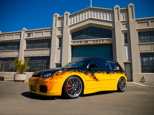 AUT 38 RK1880 01 © Kimball Stock 2003 Volkswagen GTI 20th Anniversary Yellow With Flames Low 3/4 Side View On Pavement