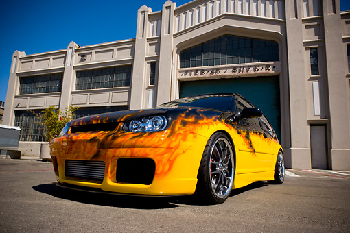 AUT 38 RK1881 01 © Kimball Stock 2003 Volkswagen GTI 20th Anniversary Yellow With Flames Low 3/4 Front View On Pavement