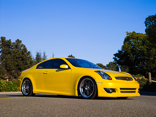 AUT 38 RK1889 01 © Kimball Stock 2003 Infiniti G35 Yellow   Low 3/4 Side View On Pavement By Trees