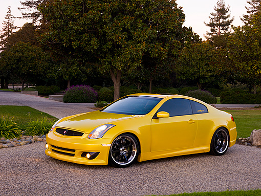 AUT 38 RK1892 02 © Kimball Stock 2003 Infiniti G35 Yellow   Side 3/4 View On Pavement By Trees And Bushes
