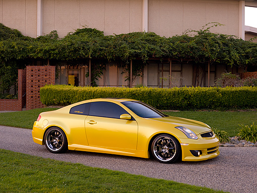 AUT 38 RK1893 01 © Kimball Stock 2003 Infiniti G35 Yellow   Side 3/4 View On Pavement By Trees And Bushes