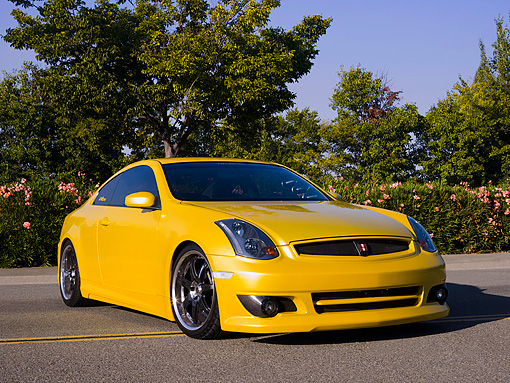 AUT 38 RK1894 01 © Kimball Stock 2003 Infiniti G35 Yellow Low 3/4 Front View On Pavement By Trees