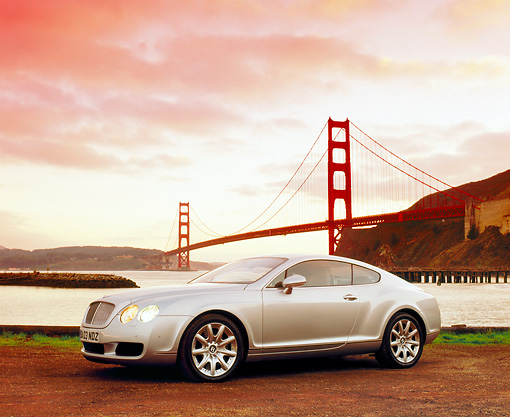 AUT 39 RK0084 05 © Kimball Stock 2004 Bentley Continental GT Silver Low 3/4 Side View On Dirt By SF Bridge Filtered