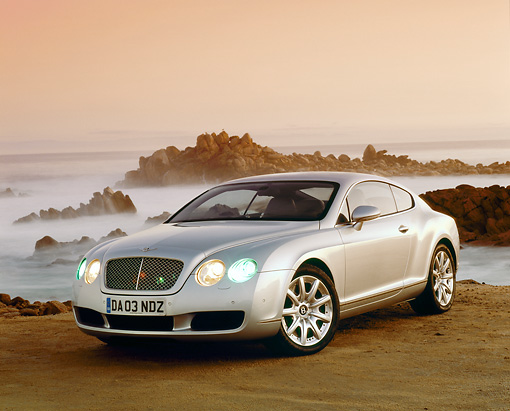 AUT 39 RK0096 03 © Kimball Stock 2004 Bentley Continental GT Silver 3/4 View On Sand By Ocean And Rocks Filtered