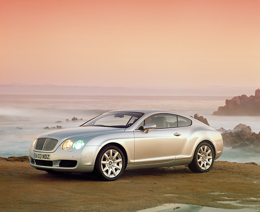 AUT 39 RK0097 02 © Kimball Stock 2004 Bentley Continental GT Silver 3/4 Side View On Sand By Ocean Filtered