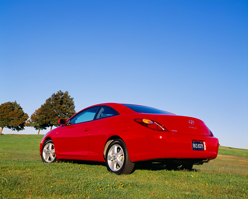 AUT 39 RK0050 03 © Kimball Stock 2004 Toyota Camry Solara Red Low 3/4 Rear View On Grass Blue Sky