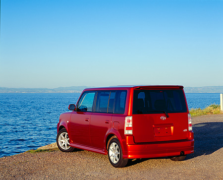 AUT 39 RK0198 02 © Kimball Stock 2004 Toyota Scion XB Orange Rear 3/4 View On Pavement By Water Blue Sky