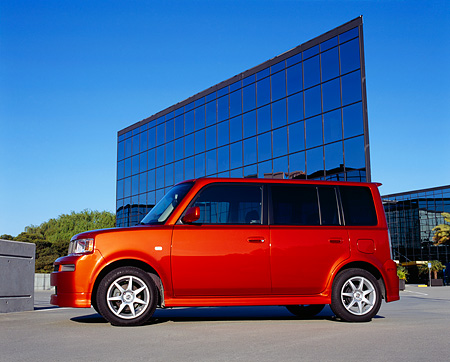 AUT 39 RK0199 02 © Kimball Stock 2004 Toyota Scion XB Orange Low 3/4 Side View On Pavement By Glass Building