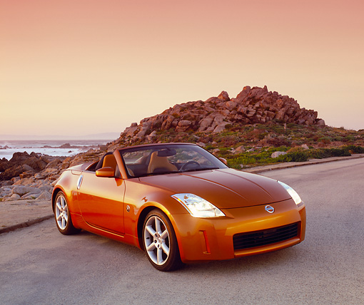 AUT 39 RK0217 03 © Kimball Stock 2004 Nissan 350Z Roadster Orange Sunset Front 3/4 View On Pavement By Coast