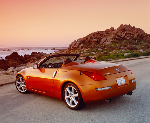 AUT 39 RK0218 04 © Kimball Stock 2004 Nissan 350Z Roadster Orange 3/4 Rear View On Pavement By Coast