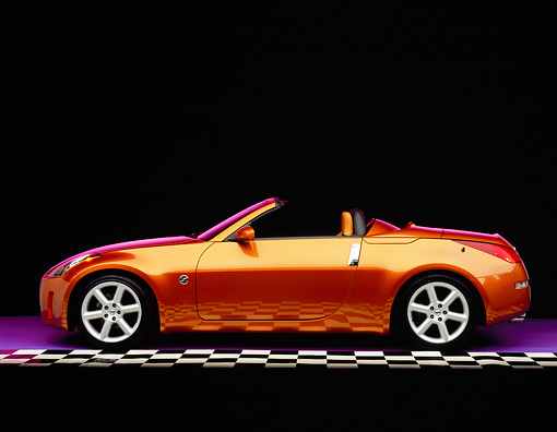 AUT 39 RK0224 01 © Kimball Stock 2004 Nissan 350Z Roadster Orange Profile View On Checkerboard Studio