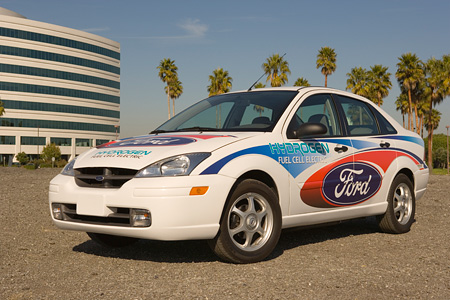 AUT 39 RK0342 01 © Kimball Stock 2004 Ford, Focus, Hydrogen Fuel Cell Electric Car 3/4 Front View On Pavement By Building