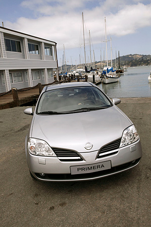 AUT 39 RK0353 01 © Kimball Stock 2004 Nissan Primera Silver Wagon 3/4 Front View On Pavement By Harbor