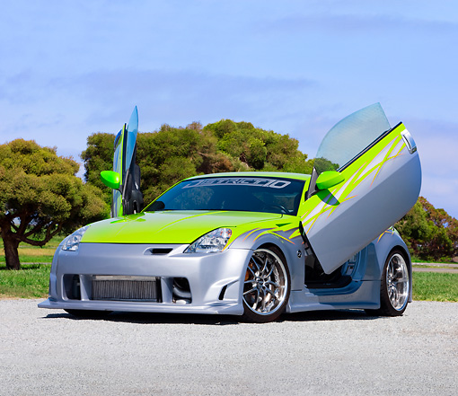 AUT 39 RK0372 01 © Kimball Stock 2004 Nissan 350Z Green And Silver 3/4 Front View By Trees Blue Sky
