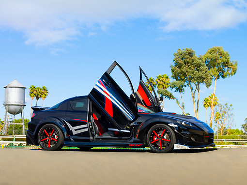 AUT 39 RK0406 01 © Kimball Stock 2004 Mazda RX-8 Custom Black 3/4 Front View Doors Open On Pavement By Trees Blue Sky