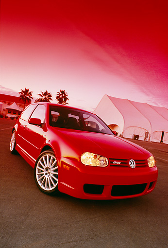 AUT 40 RK0002 02 © Kimball Stock 2005 Volkswagen R32 Golf Red 3/4 Front View On Pavement By Building Palm Trees