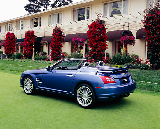 AUT 40 RK0054 01 © Kimball Stock 2005 Chrysler Crossfire SRT-6 Convertible Blue 3/4 Rear View On Grass By Building