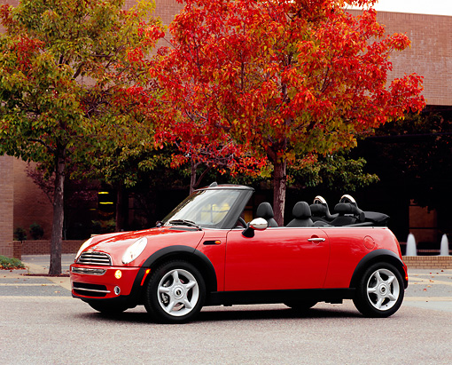 AUT 40 RK0075 02 © Kimball Stock 2005 Mini Cooper Convertible Orange 3/4 Side View On Pavement By Fall Trees And Buildings