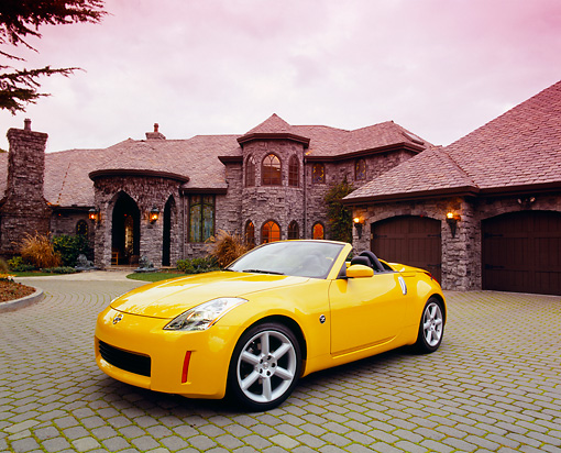 AUT 40 RK0097 03 © Kimball Stock 2005 Nissan 350Z Roadster Yellow 3/4 Front View On Driveway By House Filtered