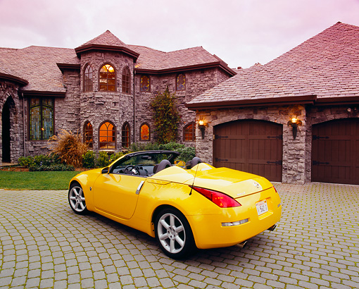 AUT 40 RK0104 02 © Kimball Stock 2005 Nissan 350Z Roadster Yellow 3/4 Rear View On Driveway By House Filtered