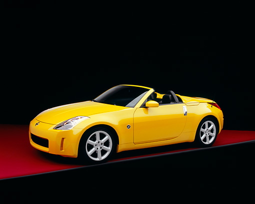 AUT 40 RK0106 07 © Kimball Stock 2005 Nissan 350Z Roadster Yellow 3/4 Side View On Red Floor Studio