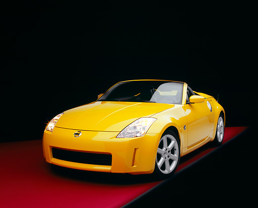 AUT 40 RK0108 07 © Kimball Stock 2005 Nissan 350Z Roadster Yellow 3/4 Front View On Red Floor Studio