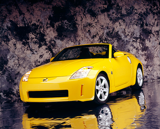 AUT 40 RK0112 02 © Kimball Stock 2005 Nissan 350Z Roadster Yellow 3/4 Front View On Mylar Floor Gray Marble Background Studio