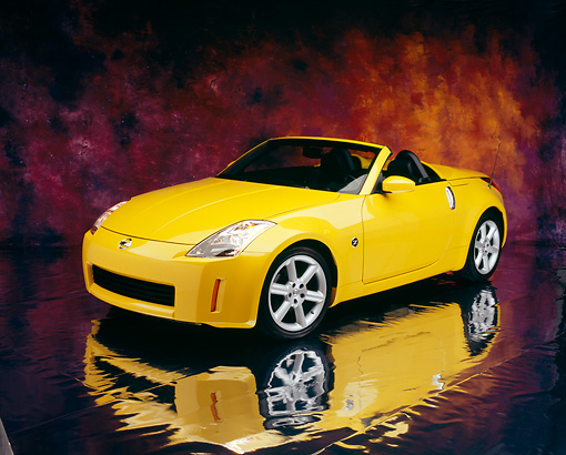 AUT 40 RK0116 06 © Kimball Stock 2005 Nissan 350Z Roadster Yellow 3/4 Front View On Mylar Floor Mottled Background Studio