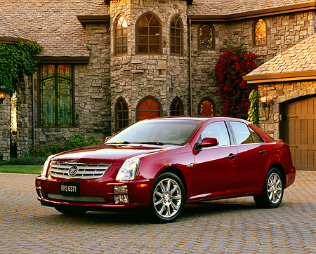 AUT 40 RK0143 02 © Kimball Stock 2005 Cadillac STS Red 3/4 Front View On Driveway By House