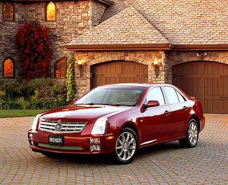 AUT 40 RK0147 05 © Kimball Stock 2005 Cadillac STS Red 3/4 Front View On Driveway By House