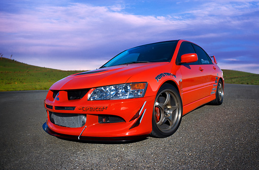 AUT 40 RK0258 01 © Kimball Stock 2005 Mitsubishi Lancer Evolution VIII Red Low 3/4 Front View On Pavement