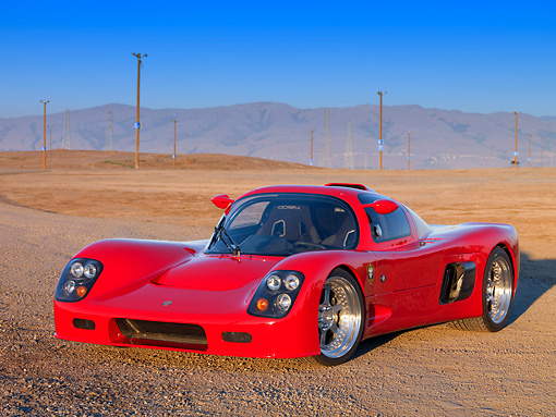 AUT 40 RK0274 01 © Kimball Stock 2005 Ultima GTR Red 3/4 Front View On Gravel By Mountains Sky