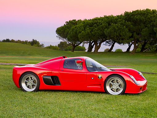 AUT 40 RK0277 01 © Kimball Stock 2005 Ultima GTR Red 3/4 Front View On Grass By Trees Sky