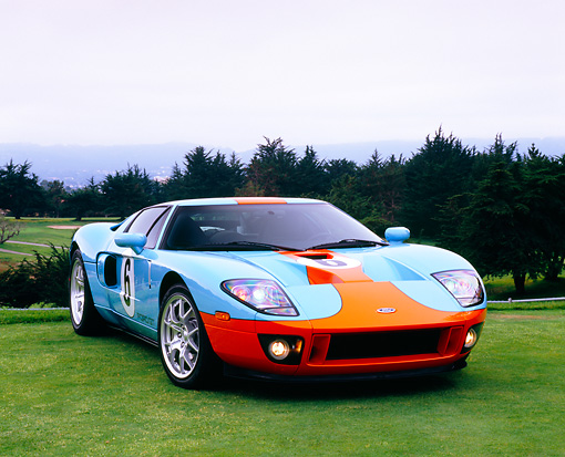 AUT 41 RK0030 06 © Kimball Stock 2006 Ford GT Light Blue And Orange 3/4 Front View On Grass By Trees