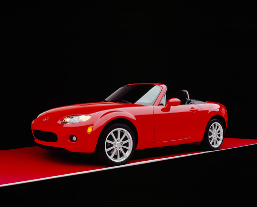 AUT 41 RK0039 08 © Kimball Stock 2006 Mazda, MX-5, Miata, Convertible Red 3/4 Side View On Red Floor Studio