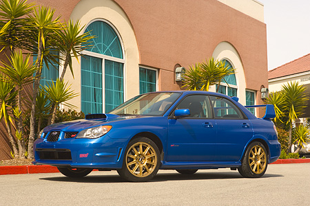 AUT 41 RK0121 01 © Kimball Stock 2006 Subaru Impreza WRX Sti Blue Low 3/4 Side View On Pavement By Building