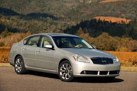 AUT 41 RK0191 01 © Kimball Stock 2006 Infiniti M35 Silver 3/4 Front View On Pavement By Hills And Trees