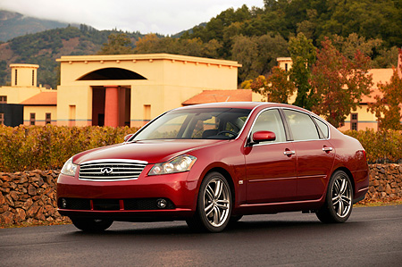 AUT 41 RK0195 01 © Kimball Stock 2006 Infiniti M45 Red 3/4 Front View On Pavement By Building And Trees